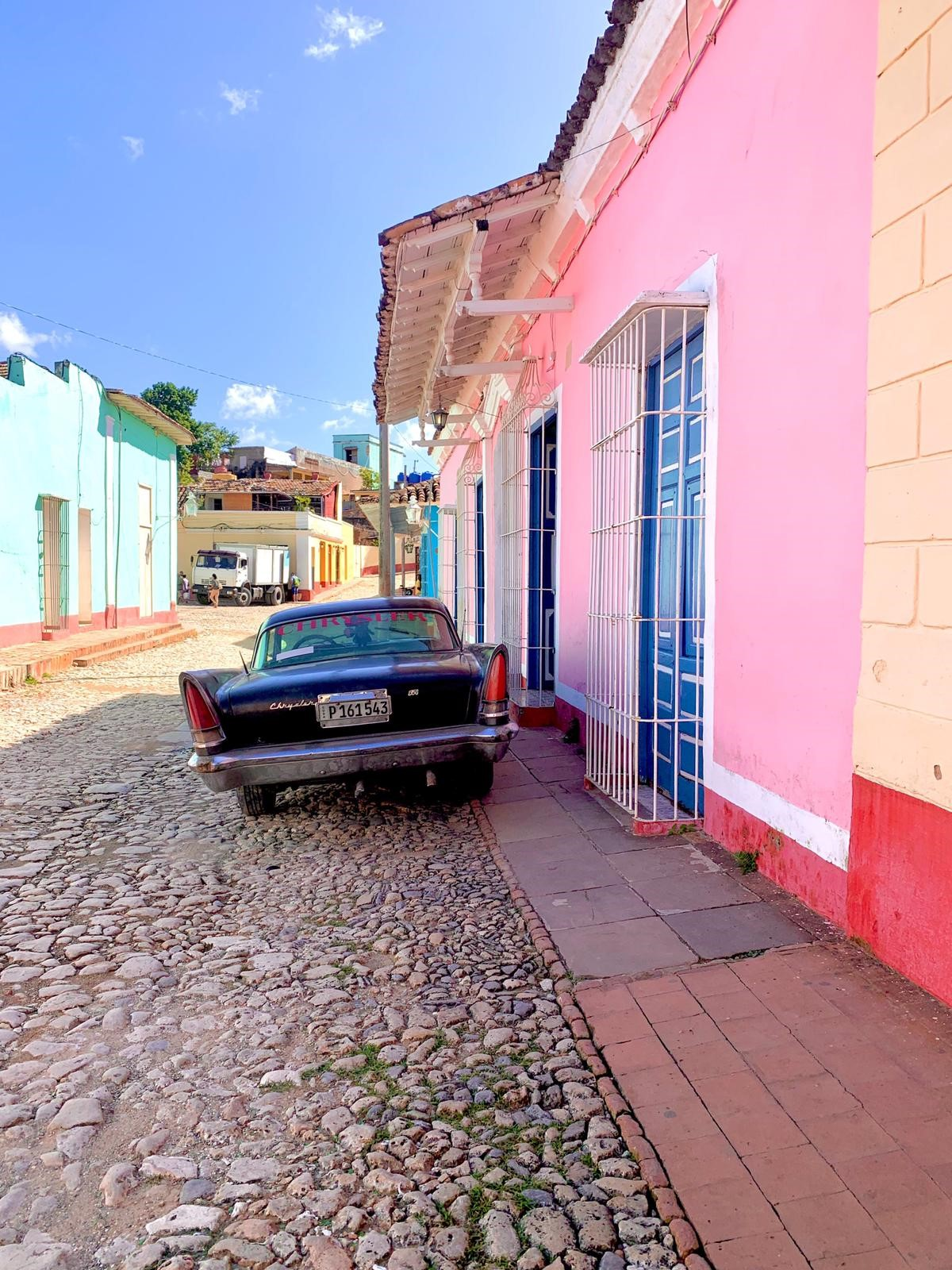 Oldtimer vor rosaner Hausfasade auf Kuba